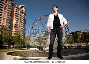 stock-photo-handsome-stylish-man-standing-near-fountain-against-city-view-164991800